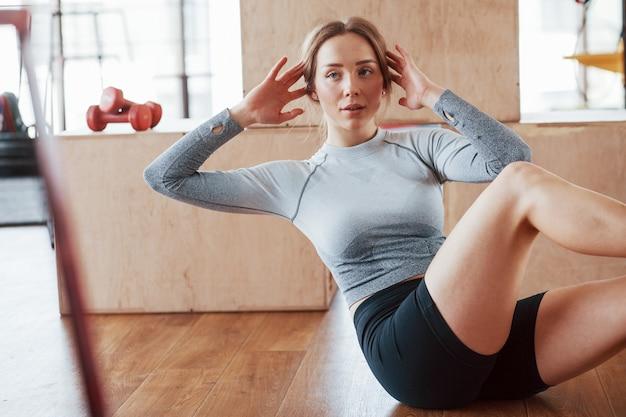 Concept de remise en forme et de style de vie. sportive jeune femme fait des abdos dans la salle de gym au matin