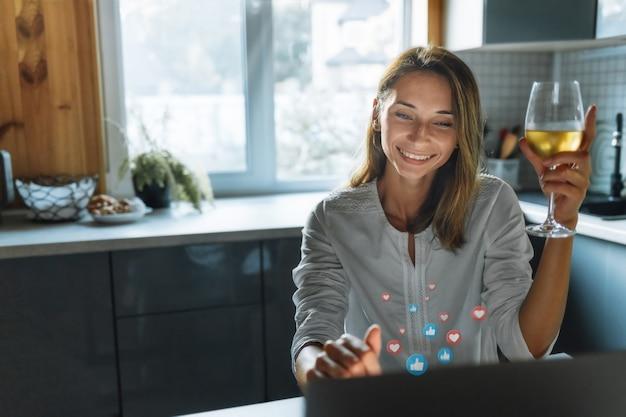 Concept de rencontre en ligne. heureuse jeune femme avec verre de vin parler via le réseau social assis à la maison dans la cuisine