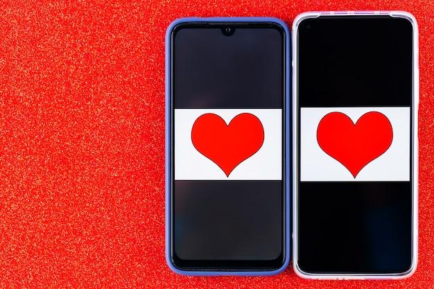 Concept de rencontres en ligne. moitiés de cœur sur les deux écrans de smartphones. concept de la saint-valentin