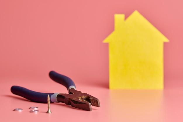 Concept de rénovation de maison. pince de monteur de lignes, vis et figurine en forme de maison jaune sur fond rose. réparation à domicile et redécorée.