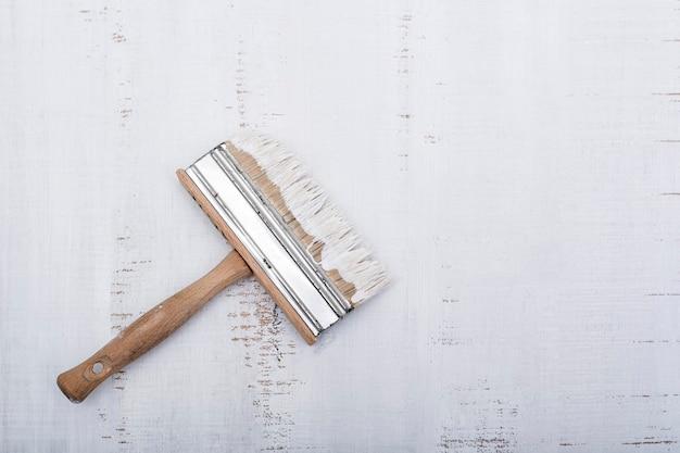 Concept de rénovation de maison. pinceau avec de la peinture sur un fond en bois minable blanc