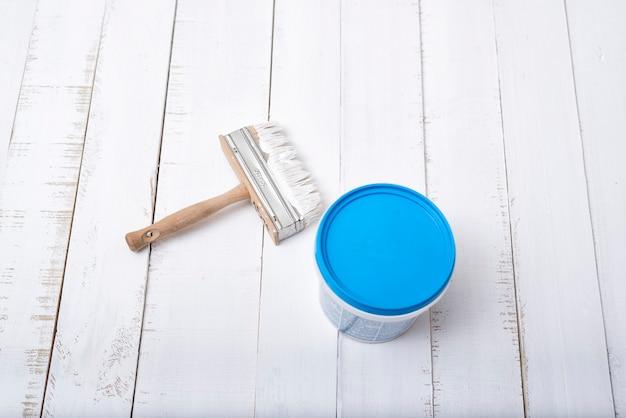Concept de rénovation de maison. pinceau et un seau de peinture sur un fond de planches de bois blanc, minable
