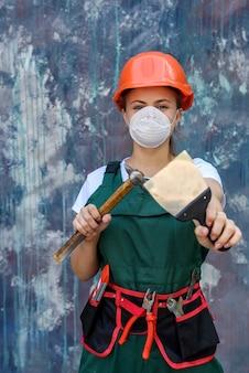 Concept de rénovation et de remodelage. femme en casque et masque de protection posant avec marteau et spatule