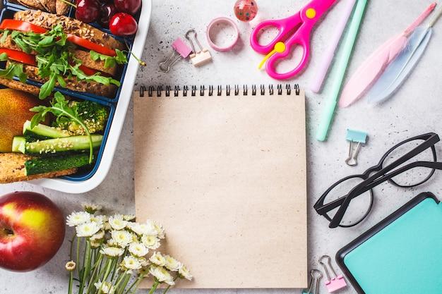 Concept de rentrée avec une boîte à lunch avec sandwich, fruits, collations, cahier, crayons et articles scolaires