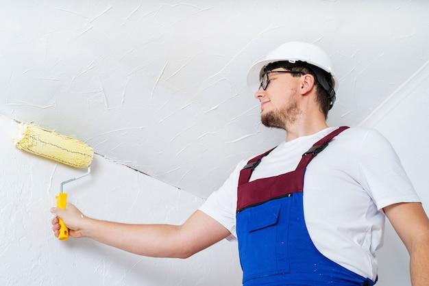 Concept de réparation, amélioration de l'habitat et rénovation. jeune homme en salopette bleue et mur de peinture casque blanc