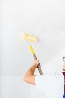 Concept de réparation, amélioration de l'habitat et rénovation. jeune homme en salopette bleue peinture mur