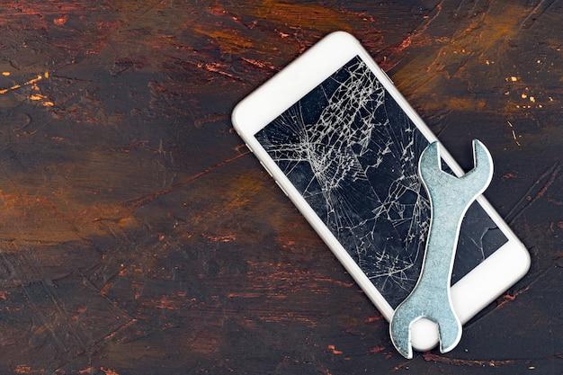 Concept de réparation de smartphone, affichage endommagé du smartphone et des outils