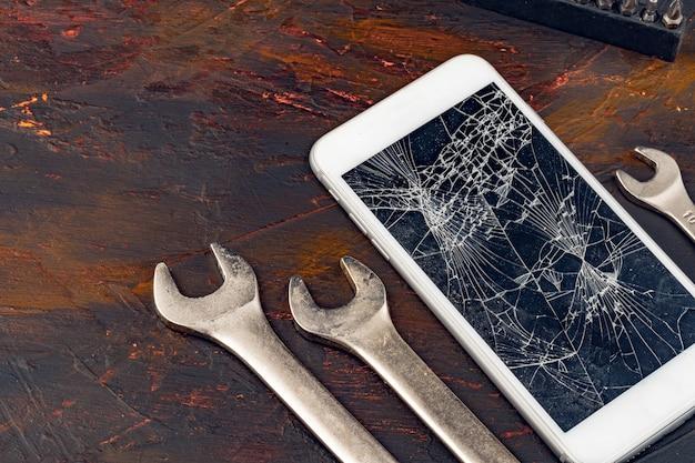 Concept de réparation de smartphone. affichage endommagé du smartphone et des outils