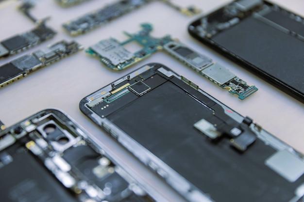 Concept de réparation de téléphone plusieurs appareils électroniques démontés dans les composants tels que les couvercles, les circuits imprimés, les corps.