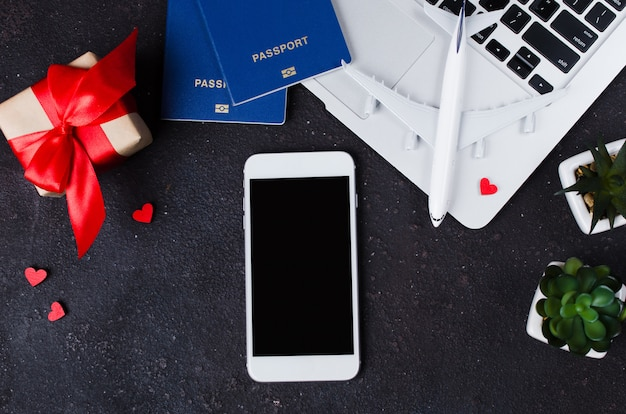 Concept de réservation de voyage. smartphone, modèle d'avion, ordinateur portable, passeports et coffret cadeau sur fond sombre.