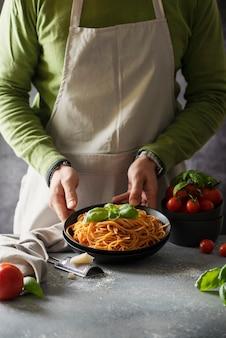 Concept de restaurant. homme cuisine spaghetti italien à la tomate et basilic, image de mise au point sélective