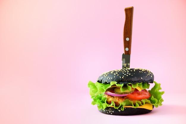 Concept de restauration rapide. burger noir juteux avec un couteau sur fond rose. repas à emporter. cadre de régime malsain avec espace de copie