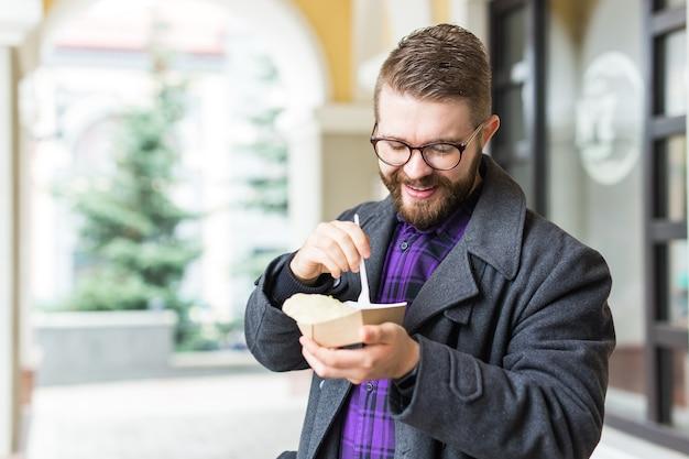 Concept de restauration rapide et de repas - jeune homme mangeant des plats à emporter dans la rue