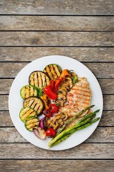 Concept de restauration saisonnière et estivale. légumes grillés et poitrine de poulet dans une assiette sur une table en bois. vue de dessus de l'arrière-plan de l'espace de copie à plat
