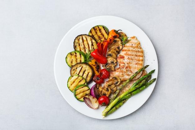 Concept de restauration saisonnière et estivale. légumes grillés et poitrine de poulet dans une assiette sur un tableau blanc. vue de dessus de l'arrière-plan de l'espace de copie à plat
