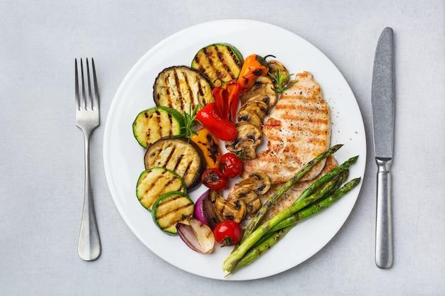 Concept de restauration saisonnière et estivale. légumes grillés et poitrine de poulet dans une assiette sur un tableau blanc. vue de dessus fond plat