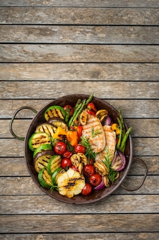 Concept de restauration saisonnière et estivale. légumes grillés et poitrine de poulet dans une casserole sur une table en bois. vue de dessus de l'arrière-plan de l'espace de copie à plat