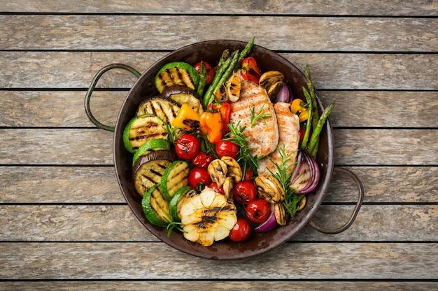 Concept de restauration saisonnière et estivale. légumes grillés et poitrine de poulet dans une casserole sur une table en bois. vue de dessus fond plat