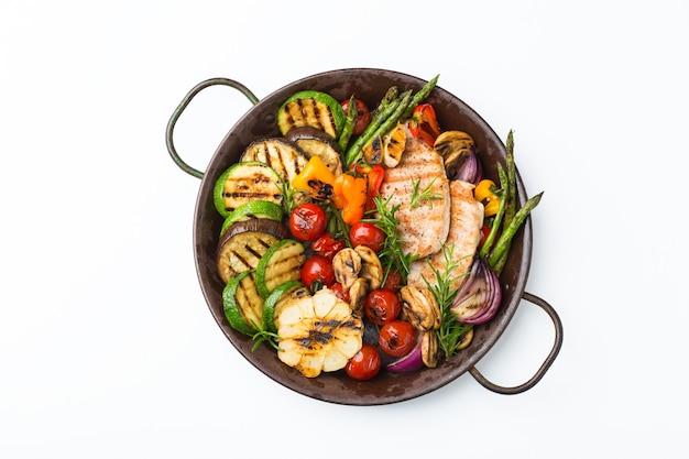 Concept de restauration saisonnière et estivale. légumes grillés et poitrine de poulet dans une casserole sur un tableau blanc, isolé. vue de dessus fond plat