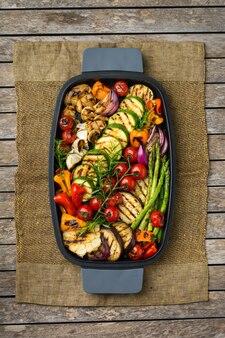 Concept de restauration végétalienne, végétarienne, saisonnière et estivale. légumes grillés dans une casserole sur une table en bois. vue de dessus fond plat