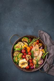 Concept de restauration végétalienne, végétarienne, saisonnière et estivale. légumes grillés dans une casserole sur une table noire foncée. vue de dessus de l'arrière-plan de l'espace de copie à plat