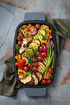 Concept de restauration végétalienne, végétarienne, saisonnière et estivale. légumes grillés dans une casserole sur une table noire foncée. vue de dessus fond plat