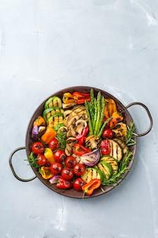 Concept de restauration végétalienne, végétarienne, saisonnière et estivale. légumes grillés dans une casserole sur une table. vue de dessus de l'arrière-plan de l'espace de copie à plat