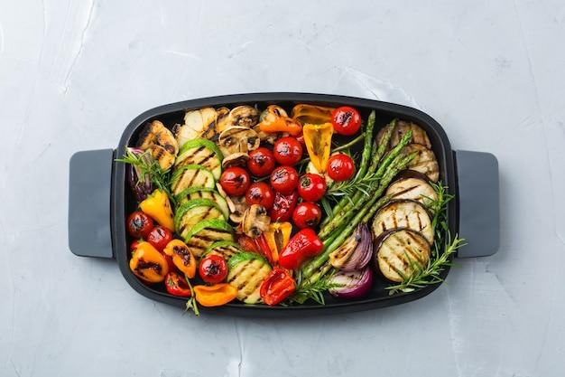 Concept de restauration végétalienne, végétarienne, saisonnière et estivale. légumes grillés dans une casserole sur une table. vue de dessus fond plat