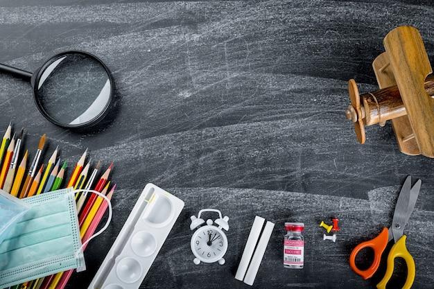 Concept de retour à l'école ou au collège vue de dessus de la papeterie des fournitures scolaires et du masque chirurgical