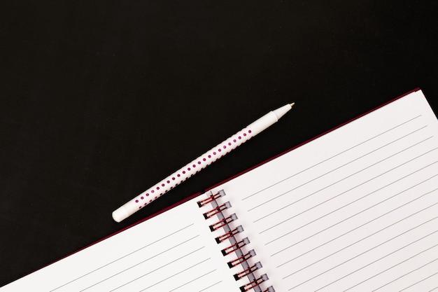Concept de retour à l'école. bloc-notes ouvert vide et stylo sur tableau noir
