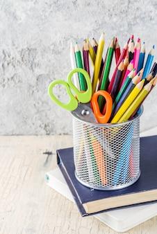 Concept de retour à l'école avec des crayons, des fournitures scolaires et des livres