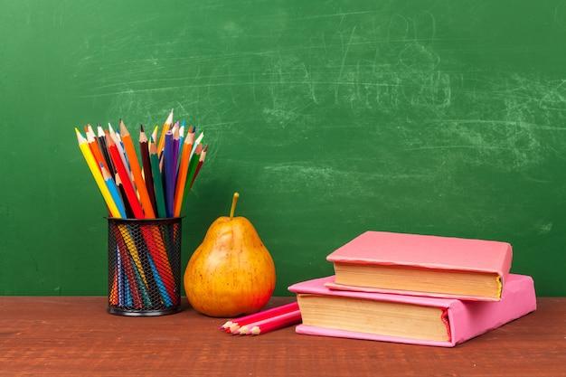 Concept de retour à l'école avec fournitures de papeterie et tableau noir