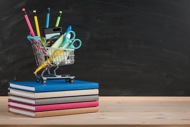 Concept de retour à l'école avec des fournitures scolaires sur fond de tableau noir