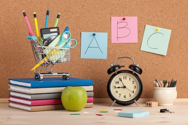 Concept de retour à l'école avec fournitures scolaires et réveil