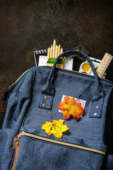 Concept de retour à l'école fournitures scolaires avec sac à dos bleu vue de dessus à plat