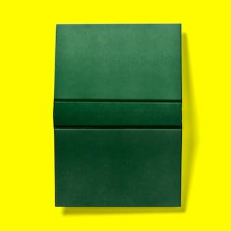 Concept de retour à l'école, livre vert foncé à couverture rigide ouvert à l'envers isolé sur jaune.