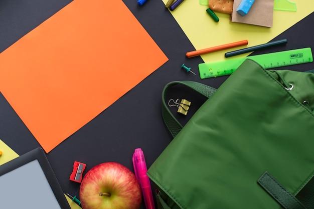 Concept de retour à l'école papeterie sac à dos apple sur fond noir.