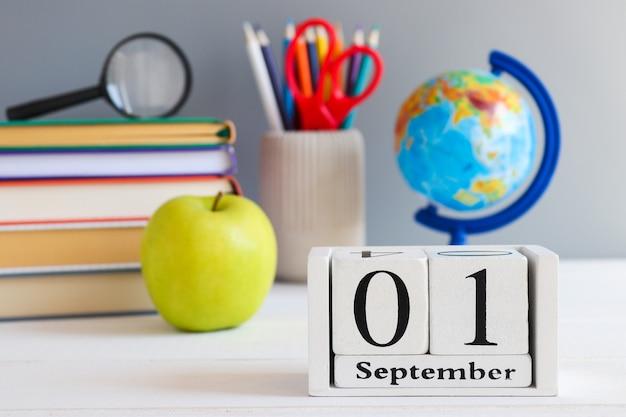 Concept de retour à l'école papeterie scolaire globe livres pomme verte et calendrier en date du 1er septembre