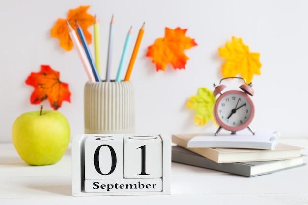 Concept de retour à l'école papeterie scolaire réveil pomme verte et calendrier daté du 1er septembre