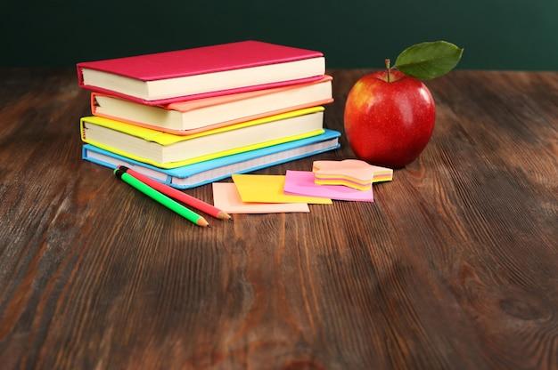 Concept de retour à l'école avec pomme, livres et accessoires