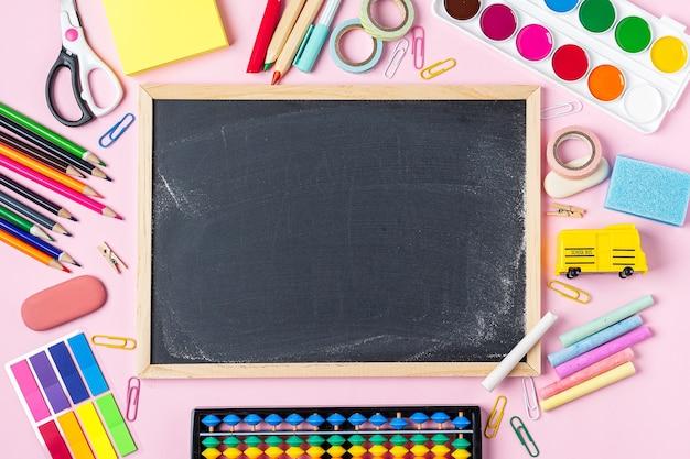 Concept de retour à la papeterie de cahier de crayon de craie de couleur d'école sur la conception de fond de tableau noir rose