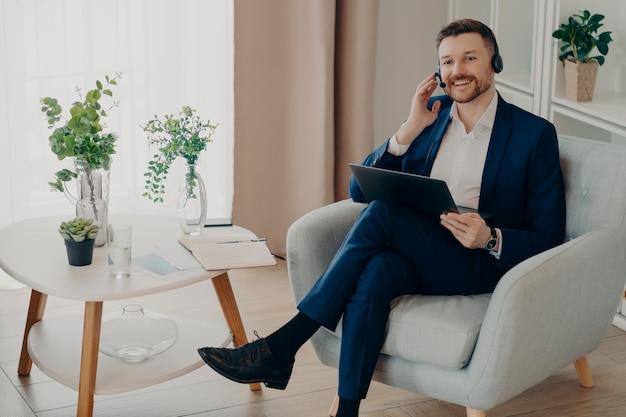 Concept de réunion en ligne. souriant employé masculin élégant en costume assis dans un fauteuil dans le salon et travaillant à distance sur un ordinateur portable, homme d'affaires ajustant le casque tout en ayant une conversation vidéo