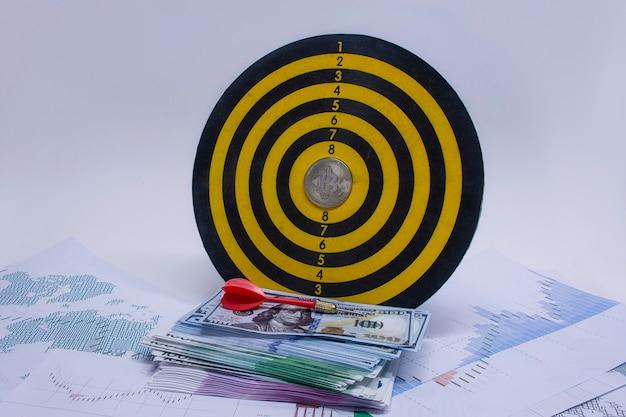 Concept de réussite et d'atteinte des objectifs. jeu de fléchettes rond avec un paquet de dollars, d'euros et une pièce de monnaie bitcoin au centre du cercle sur fond de graphiques et de diagrammes sur papier.