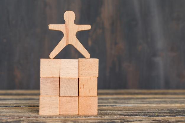 Concept de réussite commerciale avec modèle humain sur des cubes en bois sur la vue de côté de table en bois.