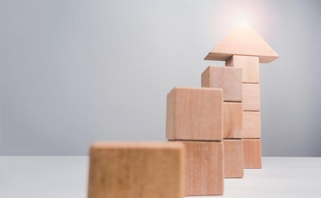 Concept de réussite de croissance d'entreprise. les blocs de bois s'empilant comme une moyenne de flèche vers le haut comme un graphique de croissance sur fond blanc avec espace de copie, style minimal et éco.