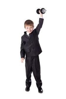 Concept de réussite mignon petit garçon en costume d'affaires avec haltère isolé sur fond blanc