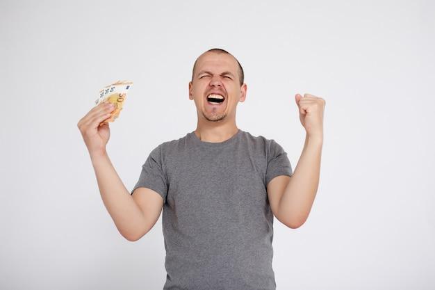 Concept de réussite, de victoire, de finance et de personnes - jeune homme gai avec de l'argent en euros célébrant quelque chose sur fond gris