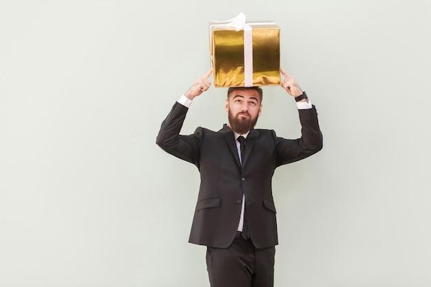 Concept de rêve ou d'idée. un homme d'affaires réfléchi rêve et tient une boîte sur une tête. prise de vue en intérieur