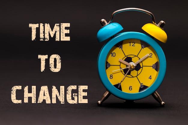 Concept, réveil avec le temps de changer la phrase écrite sur fond noir.