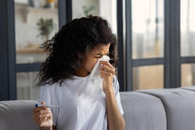 Concept de rhume et de grippe. une femme afro-américaine épuisée et malade avec un nez qui coule, des maux de tête et de la fièvre souffle la morve à l'aide d'une serviette. traitement à domicile